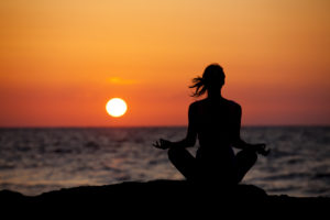 Silhouette of young woman in lotus position sitting on the beach and medditating